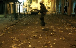 Gallery Riots in Athens: A policeman crosses a street littered with stones during riots in Athens