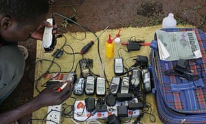 Mobile phones being charged by a car battery at Katine market