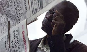 A man reads a newspaper hung up by vendors in Congo, Africa