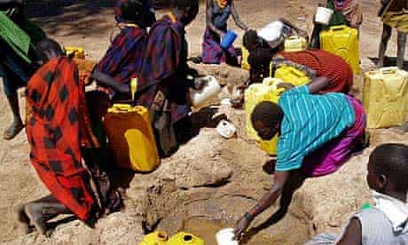 Ugandan women and children collect water from a hole dug in a dry riverbed at Kaabong village, Karamoja region