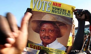 A supporter of Uganda's ruling National Resistance Movement lifts an election poster of president Yoweri Museveni