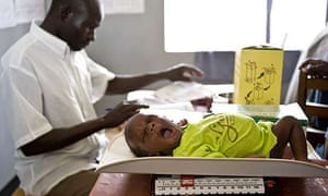 Issac Olyaka, aged 11 days, is weighed during an immunisation programme at the Ojom health centre, Katine