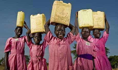 Schoolgirls from Katine primary school carry water in the village