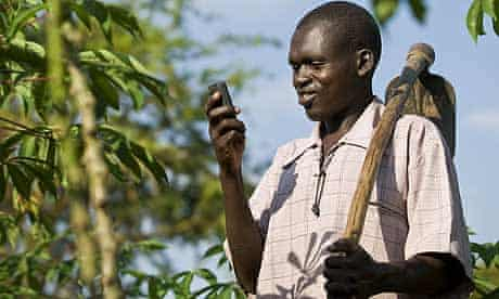 Katine farmer Dan Ekongu with his mobile phone, which he uses to communicate about agriculture