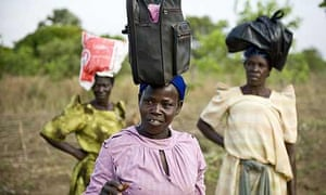 Alice Adebo and her friends carry bags on their heads in Amorikot, Katine