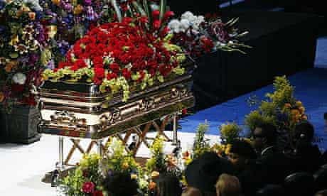 Michael Jackson's body rests inside a golden casket on the stage at the Staples Centre