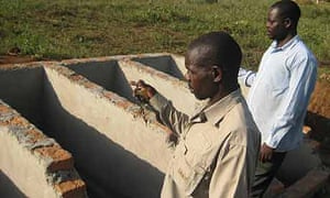 Obyarai headteacher John Ewiu and the chairman of the school management committee, Michael Ebalu, stand where the Ecosan latrine should be built in Katine