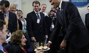 Barack Obama presents cupcakes with a candle to journalist Helen Thomas at the White House. The president and Thomas share a birthday