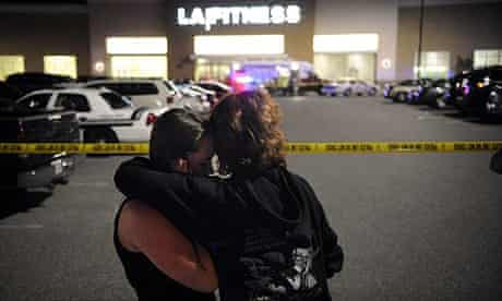 Two women embrace at the scene of a shooting at a fitness centre in Bridgeville, Pennsylvania