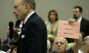 Tom Davis holds a sign as US senator Arlen Specter speaks during a town hall meeting in Lebanon, Pennsylvania.