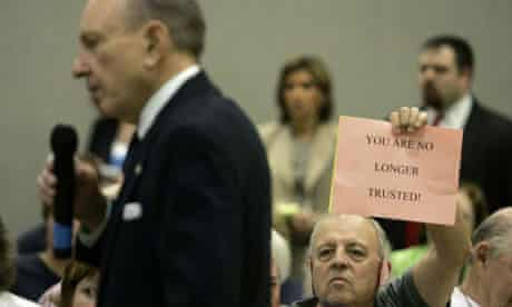 Tom Davis holds a sign as US senator Arlen Specter speaks during a town hall meeting in Lebanon, Pennsylvania.