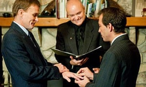 Bill Slimback, left, and Bob Sullivan exchange rings while Greg Trulson officiates at Moose Meadow lodge in Waterbury, Vermont