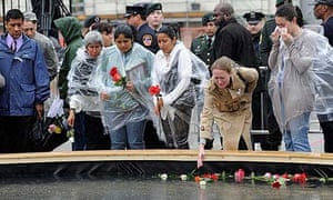 Family members of victims place flowers in a reflecting pool at Ground Zero during a 9/11 memorial ceremony in New York.