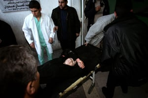 Gallery Gaza: A woman is carried into the Kamal Adwan hospital after being wounded