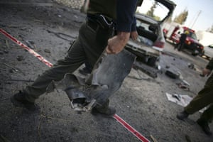 Gallery Gaza: An Israeli police explosives expert carries the remains of a rocket