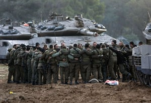 Gallery Gaza: Israeli soldiers link arms before their unit rolls toward the Gaza Strip