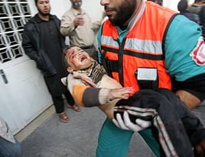 Gallery Gaza: A wounded Palestinian child is carried into the Kamal Adwan hospital