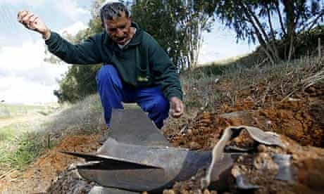 An Israeli kneels beside the remains of a rocket that landed near the town of Sderot