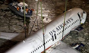 A crane moves the crashed US Airways plane from its mooring along a seawall to a barge