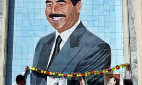 Iraqis decorate a huge mural of Saddam Hussein, 2002.