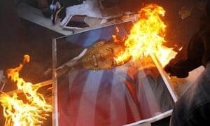 Iranian students burn a portrait of Barack Obama outside the former US embassy in Tehran