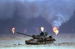 Gallery 1990s recession: A destroyed Iraqi tank rests near oil well fires during the Gulf War