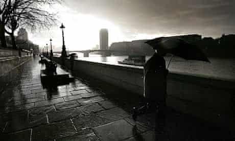 A man walks in the rain along the Albert Embankment in London