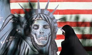 An Iranian walks past an American flag