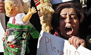 A Palestinian woman holds a doll representing wounded children at an anti-Israel protest in Nablus