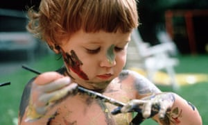 A litte child plays with paint