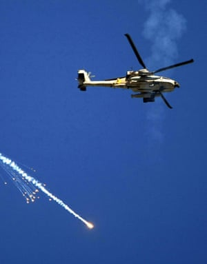 Gallery Israeli troops enter Gaza: An Israeli Apache helicopter releases a flare inside Gaza Strip