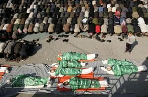 Gallery Israeli troops enter Gaza: Mourners pray near bodies of Palestinians in Gaza