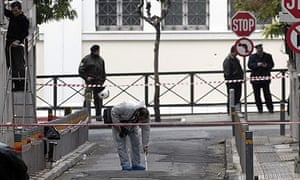 Officials investigate the scene of a shooting in Athens in which a policeman was injured.