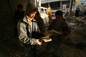 Gallery Gaza: Palestinian boys pick up pages from a torn Koran