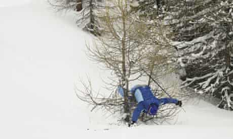 A male skier falling on a tree while skiing