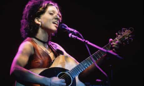 Ani DiFranco singing and playing guitar