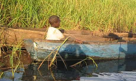 A child in a fishing boat in Merok parish, Katine. Children spend much of their time fishing instead of studying because of the drought and food shortages