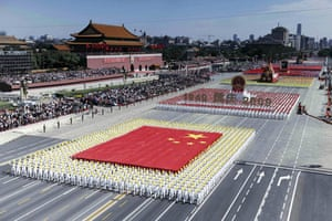 china anniversary : People in formation carry the national flag at china anniversary