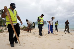 Samoa: Police use poles to poke through the sand