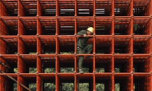 Labourer works on scaffoldings at construction site in Haikou
