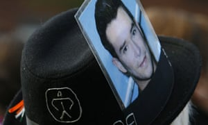 A mourning fan wears a hat with a photograph of Stephen Gately at the Boyzone star's funeral