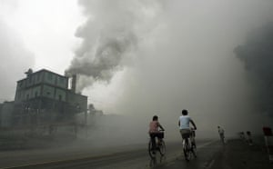 Environment decade: Cyclists pass through thick pollution from a factory in Yutian China