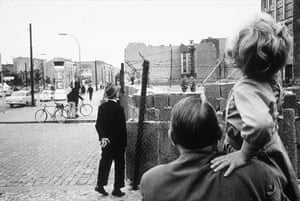 Berlin Wall: 1961: A man peers over the newly built Berlin Wall