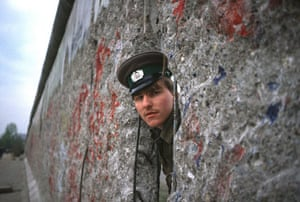 Berlin Wall: 1989: An East German border guard peers through the Berlin Wall
