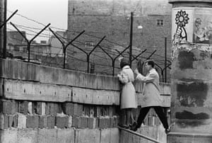 Berlin Wall: A young woman peer over the Berlin Wall to talk to her mother