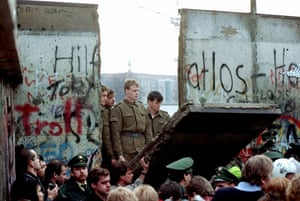 Berlin Wall: 1989: East German border guards look through a hole in the Berlin Wall