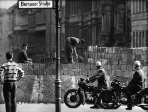 Berlin Wall: 1961: Workers building up a section of the wall in Bernauer Strasse