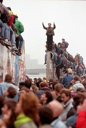 Berlin Wall: 1989: Berliners celebrate on top of the wall as East Germans flood through