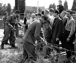 Berlin Wall: 1961: East German soldiers set up barbed wire barricades