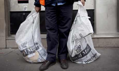 A post office worker holding bags of letters